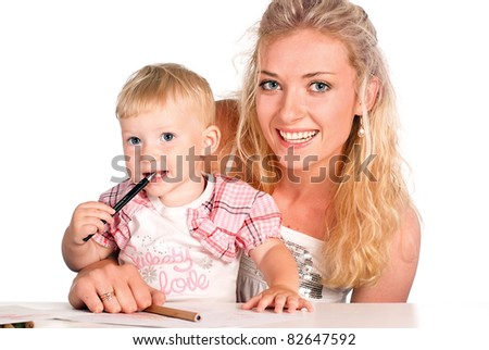 cute mom with her daughter drawing at the table - stock photo