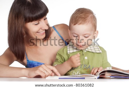 cute mom with her son reading at table