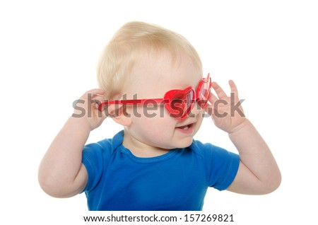 cute 18-month-old baby boy with blond hair and blue shirt wearing heart shaped sunglasses on white background - stock photo