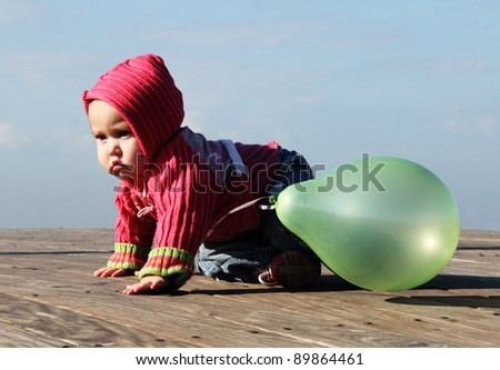cute 10-month old baby with green balloon - stock photo