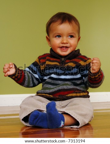 Cute 6-9 month old biracial boy happily sitting on a shiny hardwood floor. - stock photo
