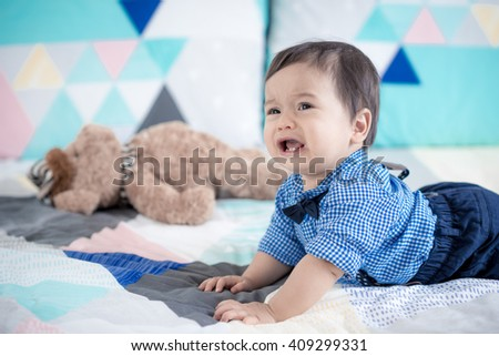 Cute 11 month old mixed race Asian Caucasian baby boy dressed up with braces and bow tie plays happily on a colourful geometric shaped bed cover with his brown teddy bear - stock photo