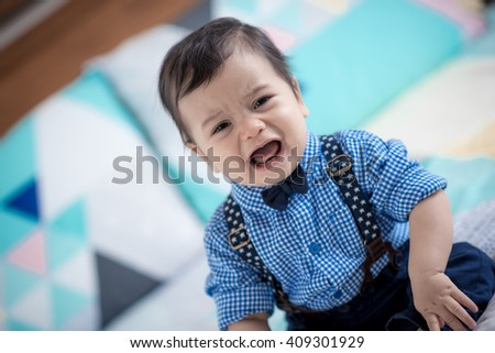 Cute 11 month old mixed race Asian Caucasian boy dressed in braces and bow tie cries sadly on a colourful geometrically shaped bed cover - stock photo