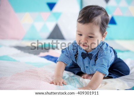 Cute 11 month old mixed race Asian Caucasian boy dressed in braces and bow tie plays cheerfully on a colourful geometrically shaped bed cover - stock photo