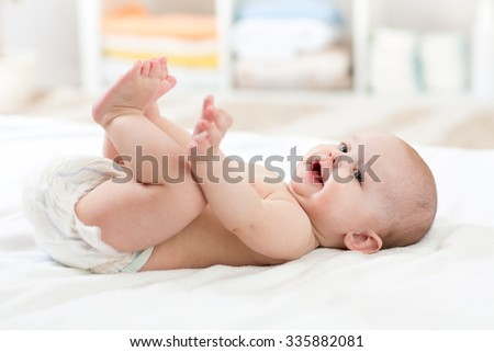 Cute 5 months baby child lying down on bed in nursery room - stock photo