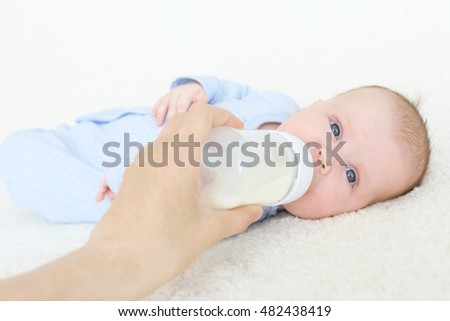 Cute 2 months baby drinking from bottle