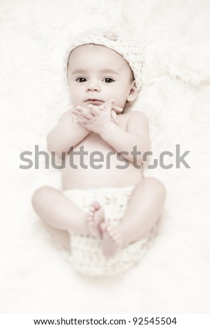 Cute 3-Months Baby wearing a  white knit hat and diaper cover
