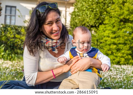 Cute 6 months old baby with Light brown hair in white, blue and brownish long-sleeved shirt is embraced and held by his mother