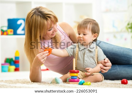 cute mother and child boy play together indoors at home - stock photo