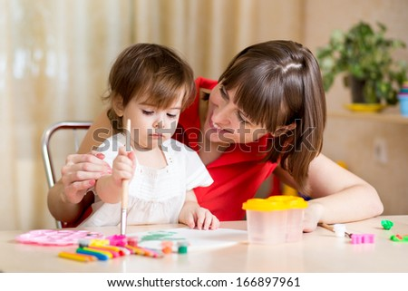 cute mother and child painting together
