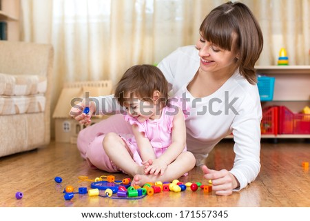 cute mother and kid girl play toys at home - stock photo