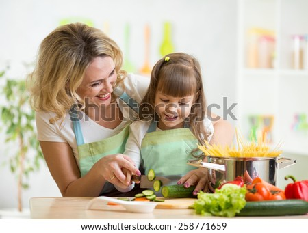 Cute mother teaches kid child cooking on kitchen - stock photo