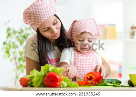 Cute mother teaches kid child on kitchen