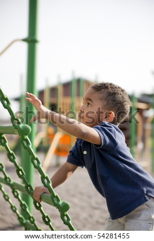 Cute multi-racial boy at the park playing - stock photo
