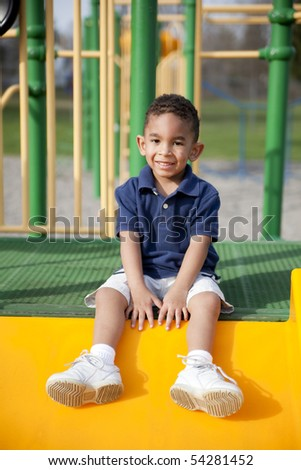 Cute multi-racial boy at the park sitting and smiling - stock photo