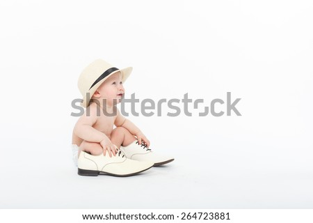 cute naked baby boy sitting on the ground with adult shoes and white hat over white background - stock photo