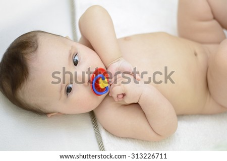 Cute naked baby lying in the crib