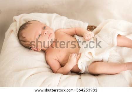 Cute naked caucasian baby boy lying under blanket on bed