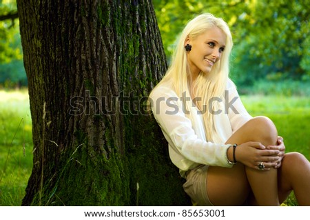 Cute natural beauty sitting in a park and relaxing against a tree - stock photo