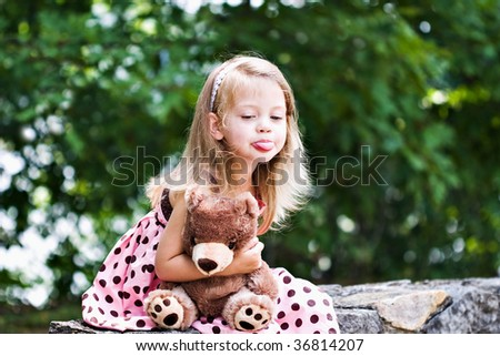 Cute, naughty child holding her teddy tightly and sticking out her tongue. Teddy is generic. - stock photo