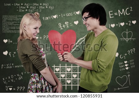 Cute nerd couple holding red heart in the classroom