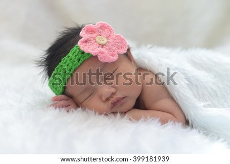 Cute newborn asian girl sleeping on furry cloth
