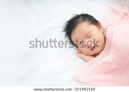 Cute newborn asian girl sleeping on furry cloth wearing roses headband - stock photo