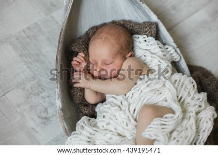 Cute newborn baby boy asleep in a bowl with a blanket. A knitted blanket. Photo Studio. Bed.