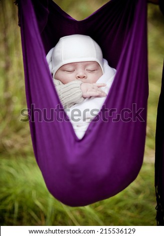 Cute newborn baby boy hanging in a baby sling outdoor - stock photo