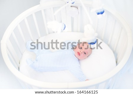 Cute newborn baby boy in a white round crib watching toys - stock photo