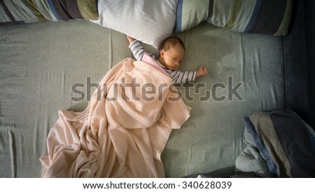 Cute newborn baby boy lying on big parents bed. View from top - stock photo