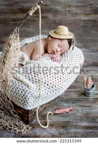 cute newborn baby boy sleeping in a hat fisherman - stock photo