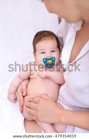 Cute newborn baby girl in her mother's arms and dummy in her mouth with white background