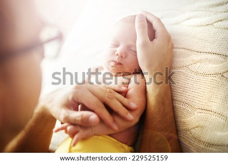 Cute newborn baby girl lying on her father's hands, at home - stock photo