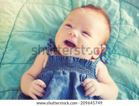 Cute newborn baby girl smiling - stock photo