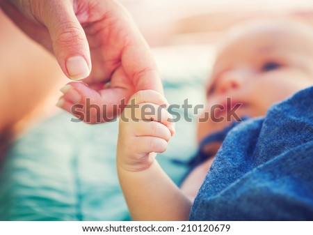 Cute newborn baby holding mother's hand - stock photo