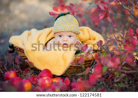 Cute newborn baby in a funny knitted hat in basket with apples