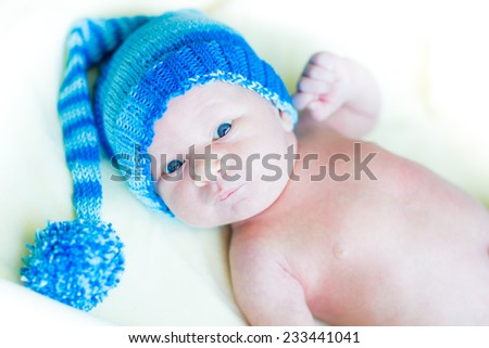 Cute newborn baby in a hat, first days - stock photo