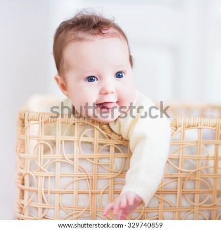 Cute newborn baby in a laundry basket. Textile and bedding for kids. Little child on a pile of towels. Adorable infant girl after bath at home. Happy laughing kid in a towel. - stock photo