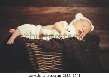 Cute newborn baby in bear hat sleeps  in basket with a toy teddy bear white - stock photo