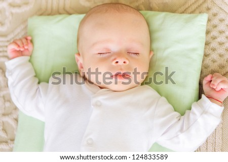Cute newborn baby sleeping in bed on pillow