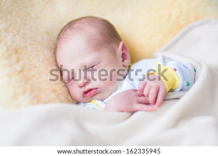 Cute newborn baby sleeping on a warm sheepskin - stock photo