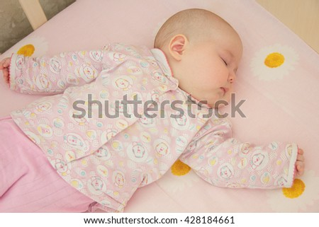 Cute newborn baby sleeps in a crib