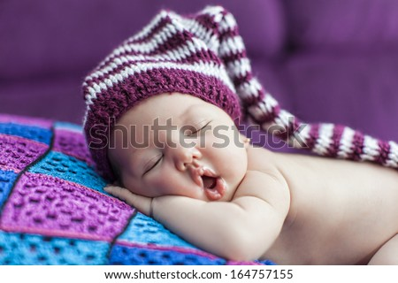 Cute newborn baby sleeps in a hat