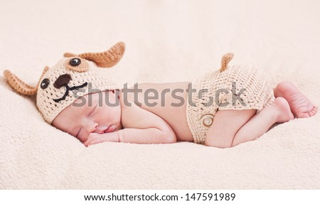 cute newborn baby sleeps in a knitted hat dogs - stock photo