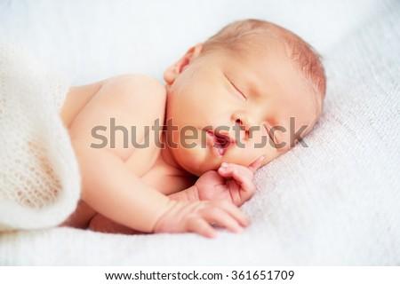 Cute newborn baby sleeps in white - stock photo
