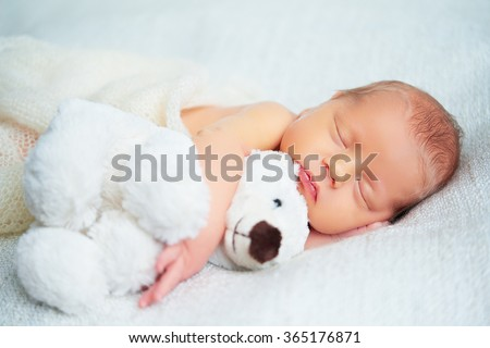 Cute newborn baby sleeps with a toy teddy bear white - stock photo
