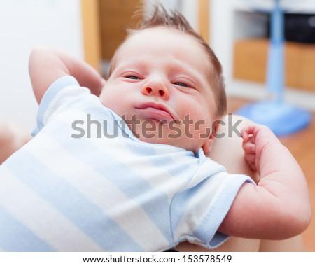 Cute newborn baby waking up and stretching - stock photo