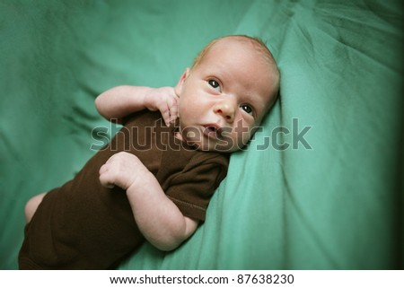 Cute newborn child on green blanket.