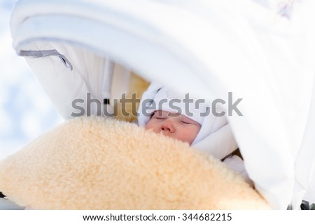 Cute newborn child sleeping in stroller on a cold winter day. New born baby taking a nap in warm sheepskin fur foot muff in a stroller in snowy park. Kids sleep outdoors in pram. Family fun in snow. - stock photo